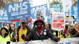 """People take part in a march in London in support of the National Health Service to demand an end to the """"crisis"""" in the NHS."""
